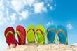 Leinwandbild Motiv Row of colorful flip flops on beach against sunny sky