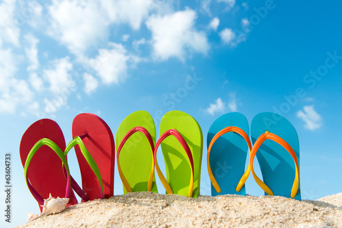 Row of colorful flip flops on beach against sunny sky - 63604733
