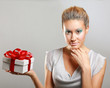 Girl opening x-mass present isolated on grey background.