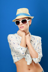 Young woman in hat and sunglasses , isolated on blue background