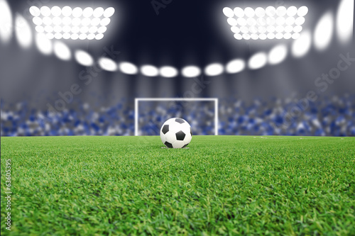 Soccer ball on field in stadium at night