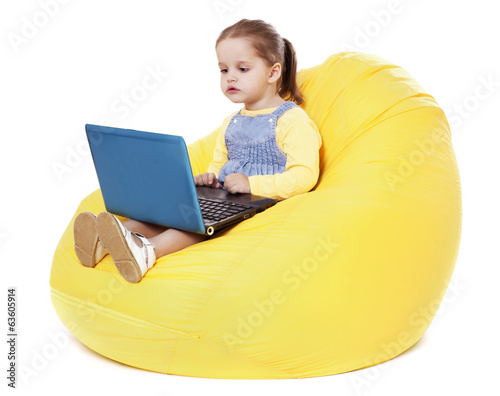 Child  sitting on a bean bag with laptop - Stock Image