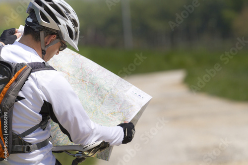Man with bike checking map and looking around