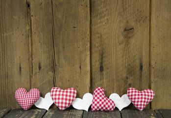 Holz Hintergrund mit rot weiß karierten Herzen