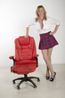 Female office worker standing with red leather chair