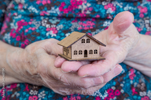 a small house on hands of a senior woman