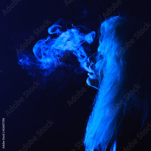 dark and sullen shot of a young woman smoking