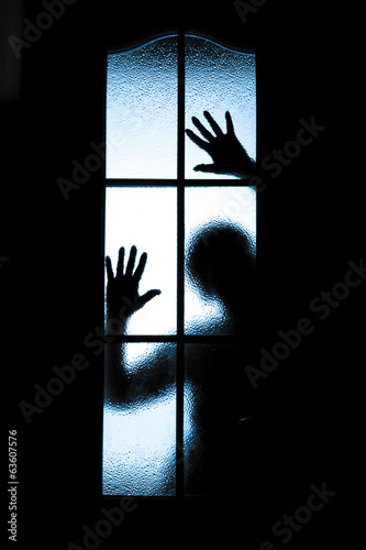 Scared boy behind glass door