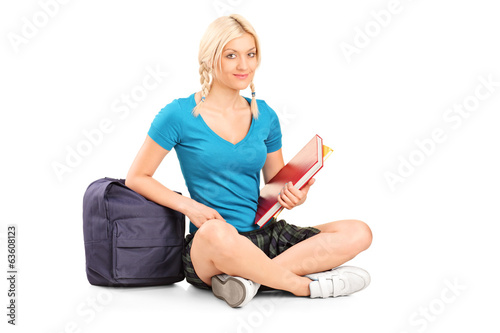 Female student holding books seated on the floor