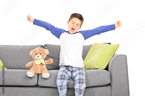 Little boy yawning seated on couch
