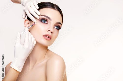 Naklejka Beautiful woman gets injections. Cosmetology. Beauty Face