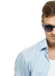 Stylish man in blue shirt wearing sunglasses isolated on white