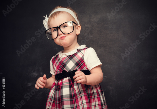 funny girl pupil in glasses at blackboard