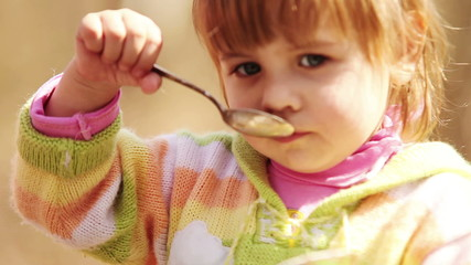 Outdoor portrait : Cute Little girl eats with spoon