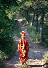 Girl in Chinese princess costume walks in forest, view from back
