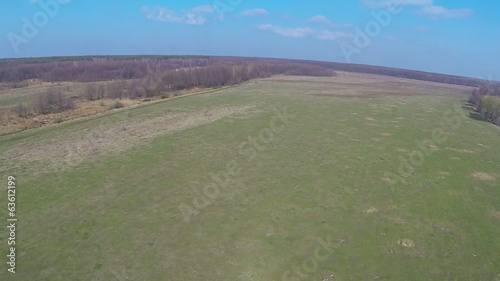 Green field and  sky with clouds. Aerial