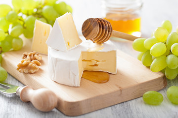 camembert cheese with grapes, honey and nuts on wooden backgroun