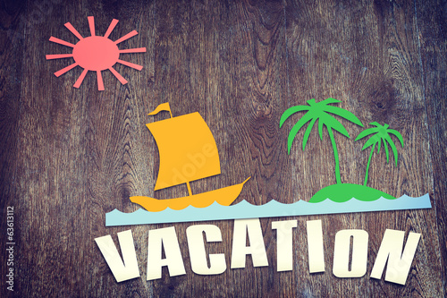 Paper scraps about summer vacation on wooden surface
