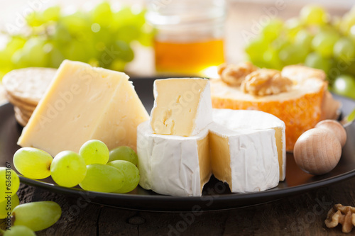 various types of cheese with grapes, honey and nuts