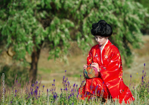 Woman in red kimono with a small parcel in summer day