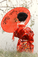 Geisha with red umbrella at the riverside (back view) © rodjulian