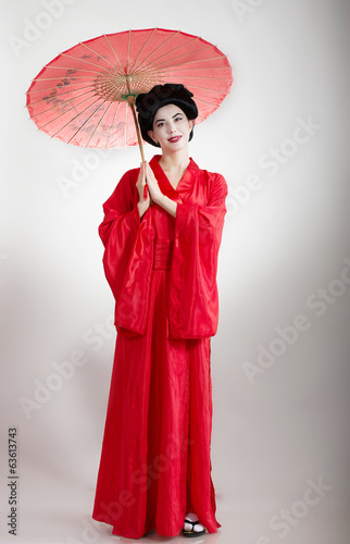 Asian style portrait of a girl in red kimono with umbrella