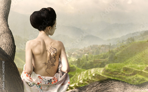 Girl with snake tattoo on her back sits on tree branch