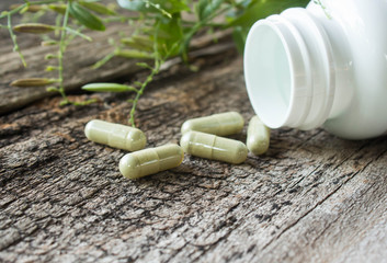 Herb capsule on old wood