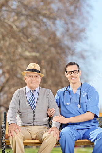 Doctor and a senior gentleman sitting outdoors