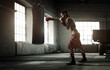 canvas print picture - Young woman boxing workout in an old building