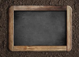 Blank chalkboard on soil background