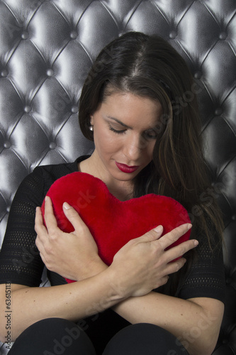 Beautiful woman hugging a red heart (gift, love, portrait)