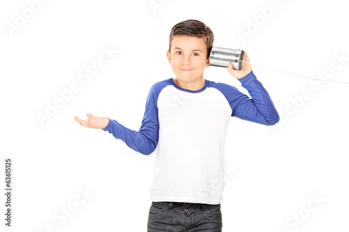 Little boy listening through a tin can phone