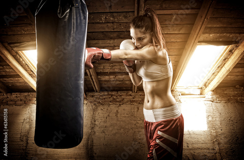 Fotobehang Vechtsporten Young woman boxing workout on the attic