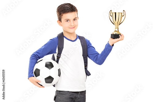 Little schoolboy holding football and a trophy