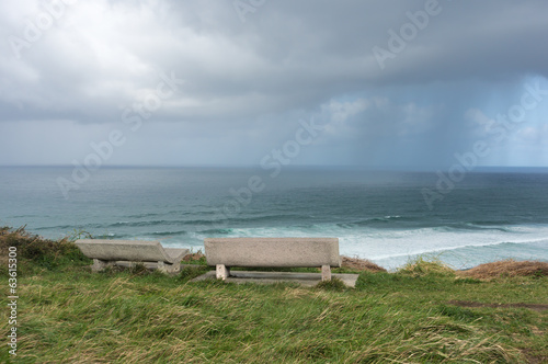 benches on cliff near the sea with stormy clouds