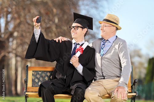 Male graduate and his father taking selfie in park