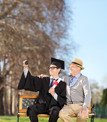 Male student and his father taking selfie in park