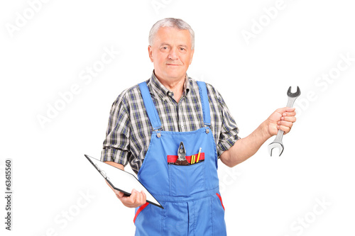 Mature mechanic holding clipboard and a wrench
