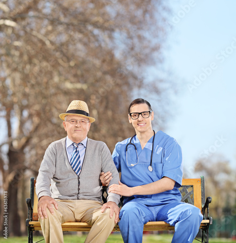 Senior man and a male doctor posing in park