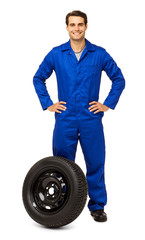 Confident Male Mechanic With Spare Tire