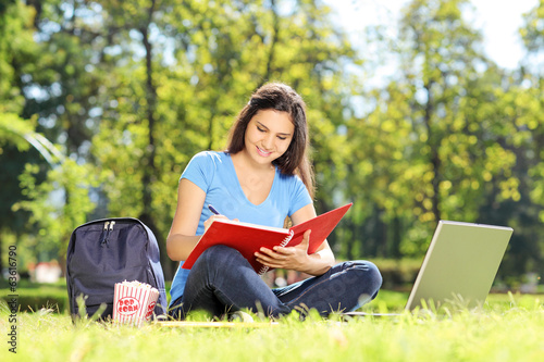 Girl sitting on grass and writing in a notebook
