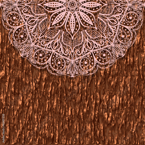 Part of a circular lace mandala ornament on of tree bark.