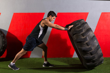 man flipping a tractor tire workout gym exercise