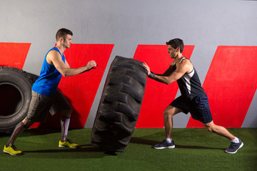 men flipping a tractor tire workout gym exercise