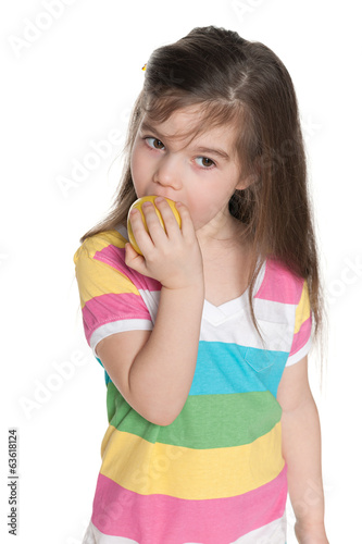 Little girl eats an apple