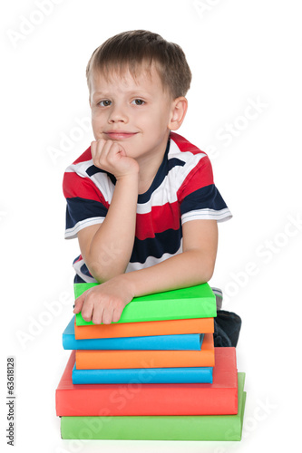 Thoughtful young boy with books