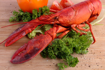Cooked lobster with various vegetables on wooden board