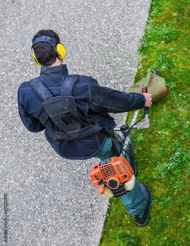 gardener using corded string trimmer in a park