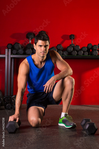 Hex dumbbells man workout in red gym